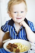 Boy sitting in front of plate of meatballs and pasta