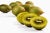 Whole and halved kiwi fruits (variety: Golden Kiwi)