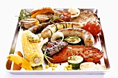 Grill platter: meat, sausages, vegetables and corn on the cob