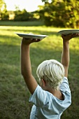 Blond boy carrying two plates