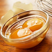 Two Cracked Eggs in a Small Glass Bowl; Shells and Whisk