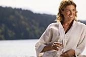 Woman wearing bathrobe, holding glass of water