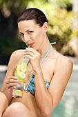 Frau im Bikini trinkt Limonade