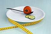 Tomato and cucumber slice on plate with measuring tape, close-up