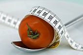 Tomato on spoon with tape measure, close-up