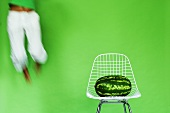 Young woman jumping by watermelon on chair, (blurred motion)