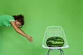 Young woman exercising by watermelon on chair, (blurred motion)