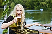 Germany, Bavaria, Munich, English Garden, Young woman holding beer stein