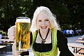 Germany, Bavaria, Munich, English Garden, Young woman holding beer stein, smiling, portrait