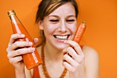 Young woman holding carrot and carrot juice, smiling, close-up