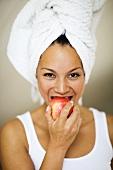 Woman in towel turban eating an apple