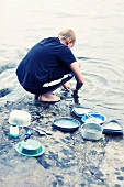 Boy rinsing dishes in river
