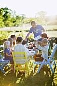 Familie mit mehreren Kindern isst im Garten