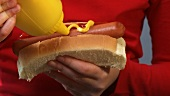 Girl putting mustard on hot dog and biting into it