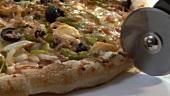 Pizza mit Pizzaschneider schneiden