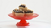 Small chocolate cream tarts with nuts on red stand