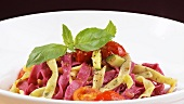 Coloured ribbon pasta with tomatoes and basil