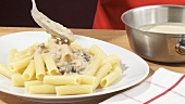 Serving out rigatoni with mushroom sauce