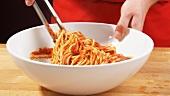 Spaghetti mit Tomatensauce vermengen
