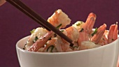 Taking prawns out of a bowl with chopsticks