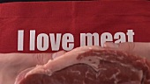 Apron with the words I love meat and piece of fresh beef