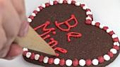 Herzförmiges Schokoladengebäck verzieren