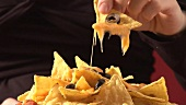 Hand holding nacho with melted cheese