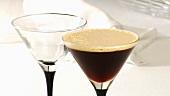 Zwei Cocktailgläser, leer und mit Cocktail