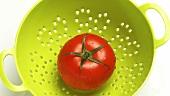 A tomato in a colander