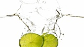 Slices of lime falling into water