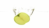 Half a green apple falling into water