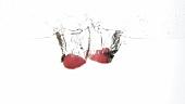 Zwei Erdbeeren fallen ins Wasser