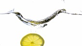 A slice of lemon falling into water