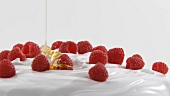 Pouring honey over cream with raspberries