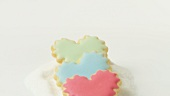 Heart-shaped biscuits with coloured icing on heap of sugar