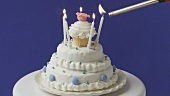 Lighting birthday candles on a white cake