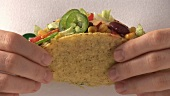 Hands holding taco with vegetable filling
