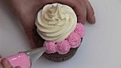 Schokoladen-Cupcake mit rosa Zuckercreme verzieren
