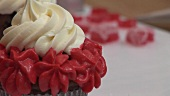 Schokoladen-Cupcake mit Sahnehaube und roter Zuckercreme