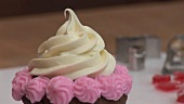 Chocolate cupcake with cream topping and pink buttercream