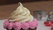 Schokoladen-Cupcake mit Sahnehaube und rosa Zuckercreme