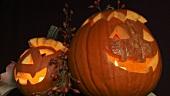 Beleuchtete Halloweenkürbisse mit Herbstlaub und Hagebutten