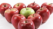 Red apples and one green apple arranged in a triangle
