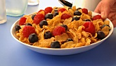 Pouring milk over cornflakes with berries