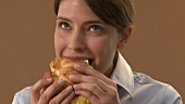 Young woman eating croissant filled with scrambled egg & cheese