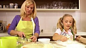 Mother and daughter baking apple tart together
