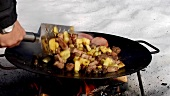 Cooking sausage and potato dish in frying pan over open fire