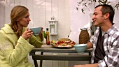 Couple at garden table with plate of food, coffee & mobile phone