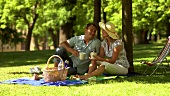 Couple picnicking in park, drinking coffee