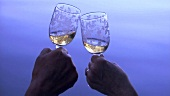 Mature hands clinking glasses of white wine